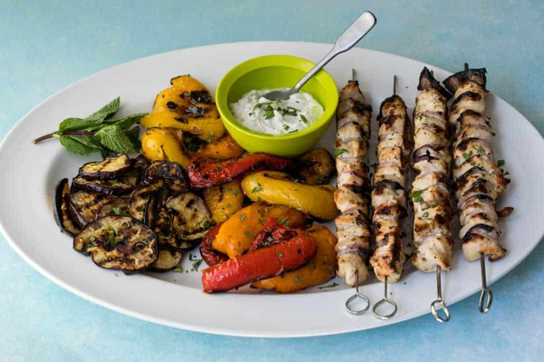 platter of grilled chicken kabobs with yogurt sauce and grilled vegetables