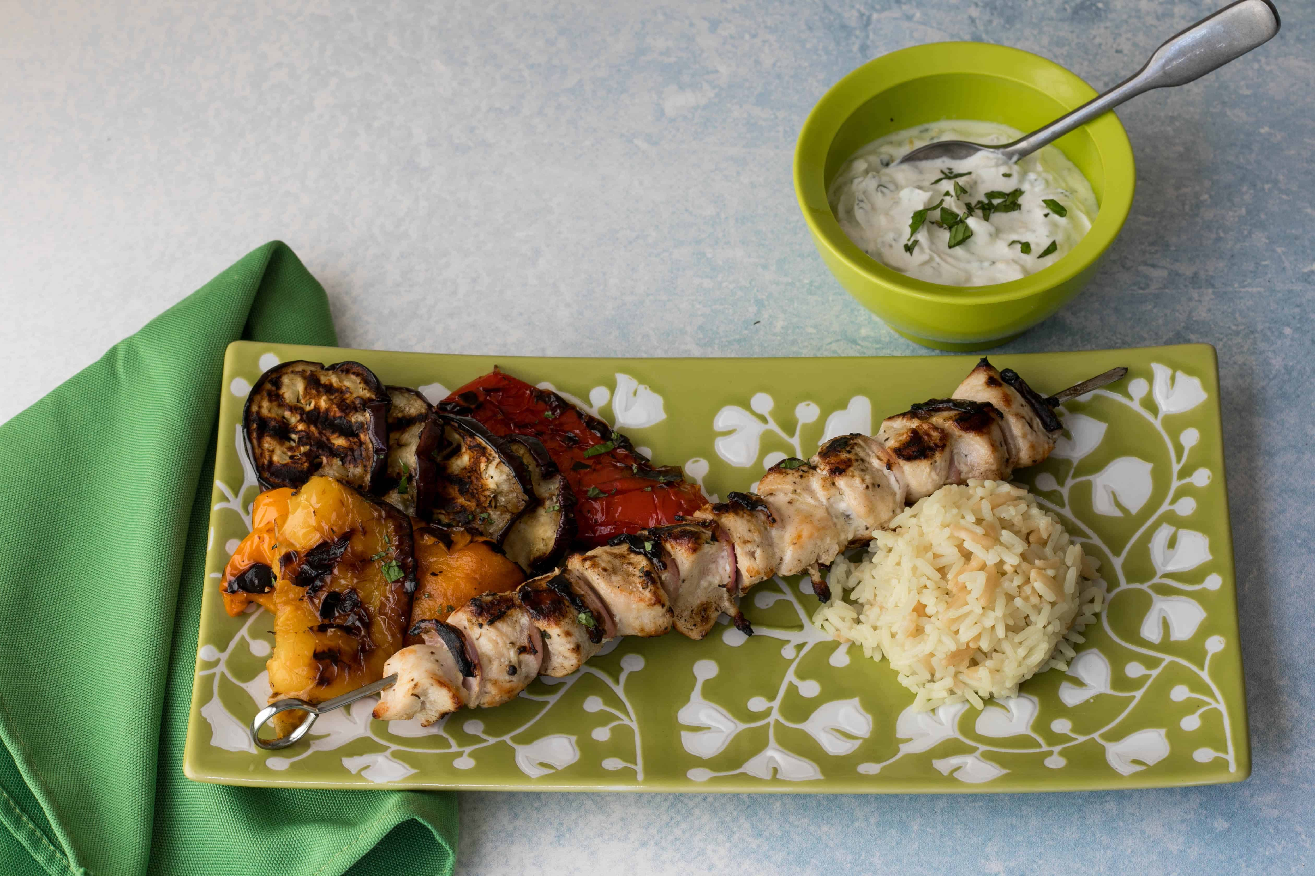 chicken kabobs with yogurt sauce, grilled vegetables, and rice pilaf