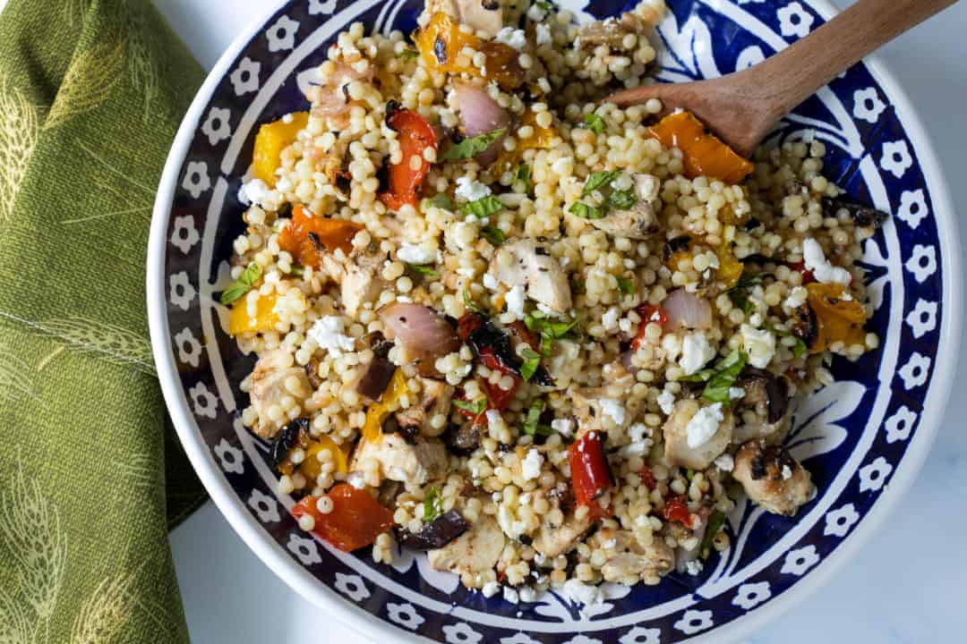 bowl of Israeli couscous with grilled chicken, vegetables, and feta cheese