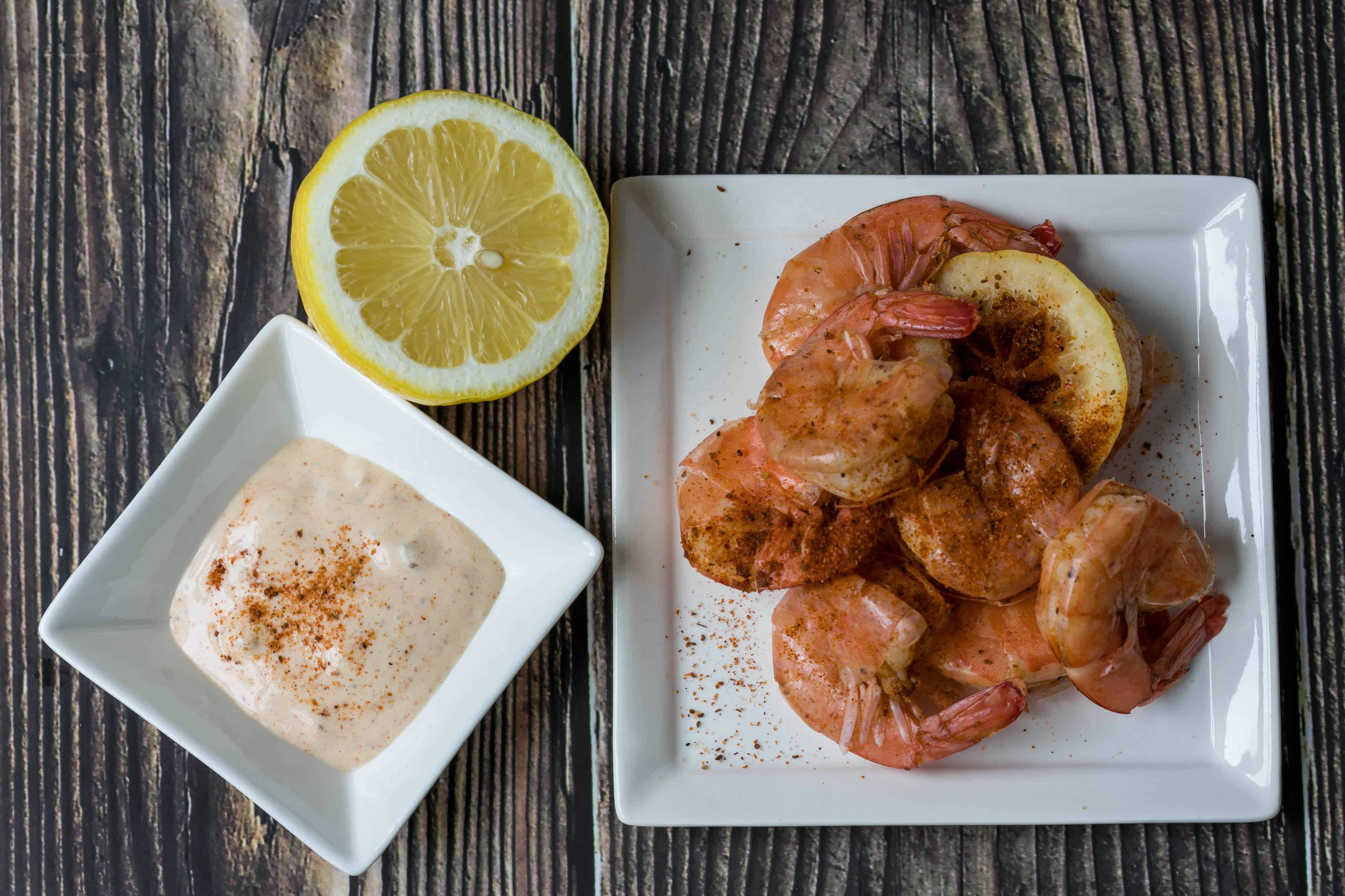 old bay spiced shrimp next to dipping sauce and lemon