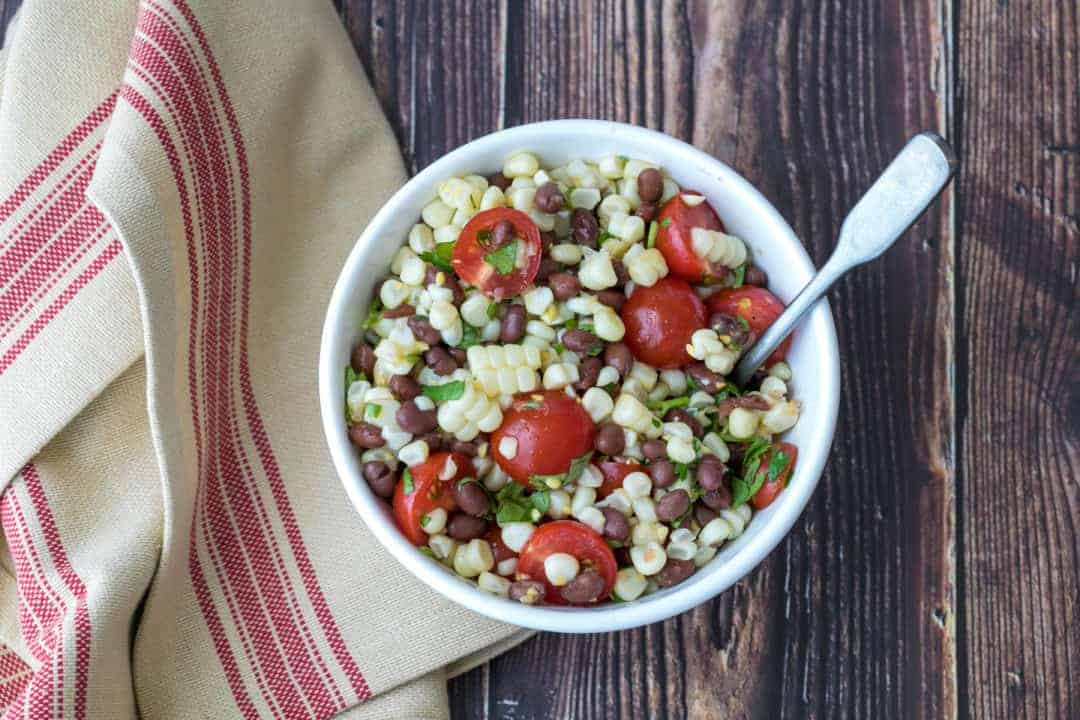 black bean and corn salad in bowl with kitchen towel