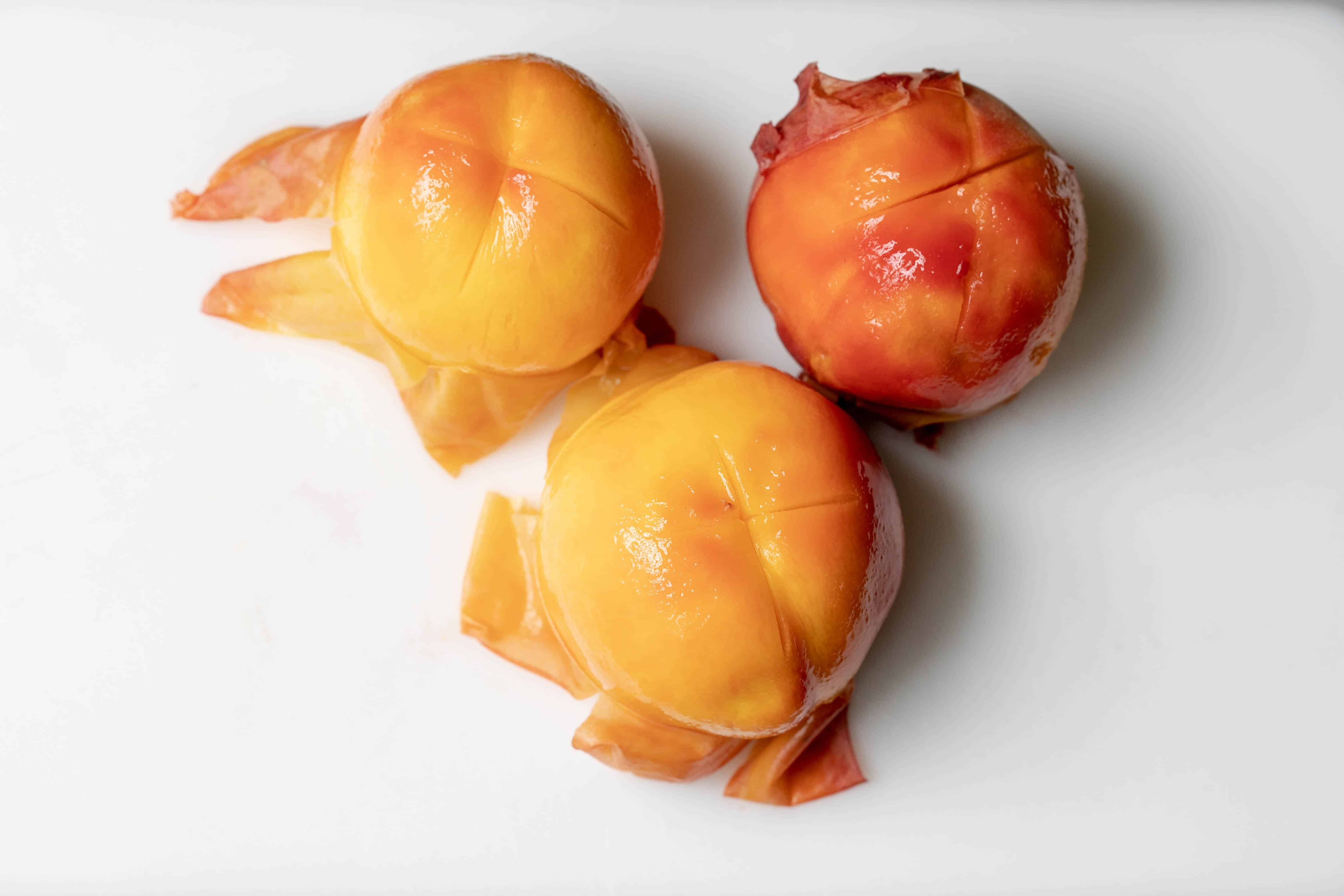 3 partly peeled peaches