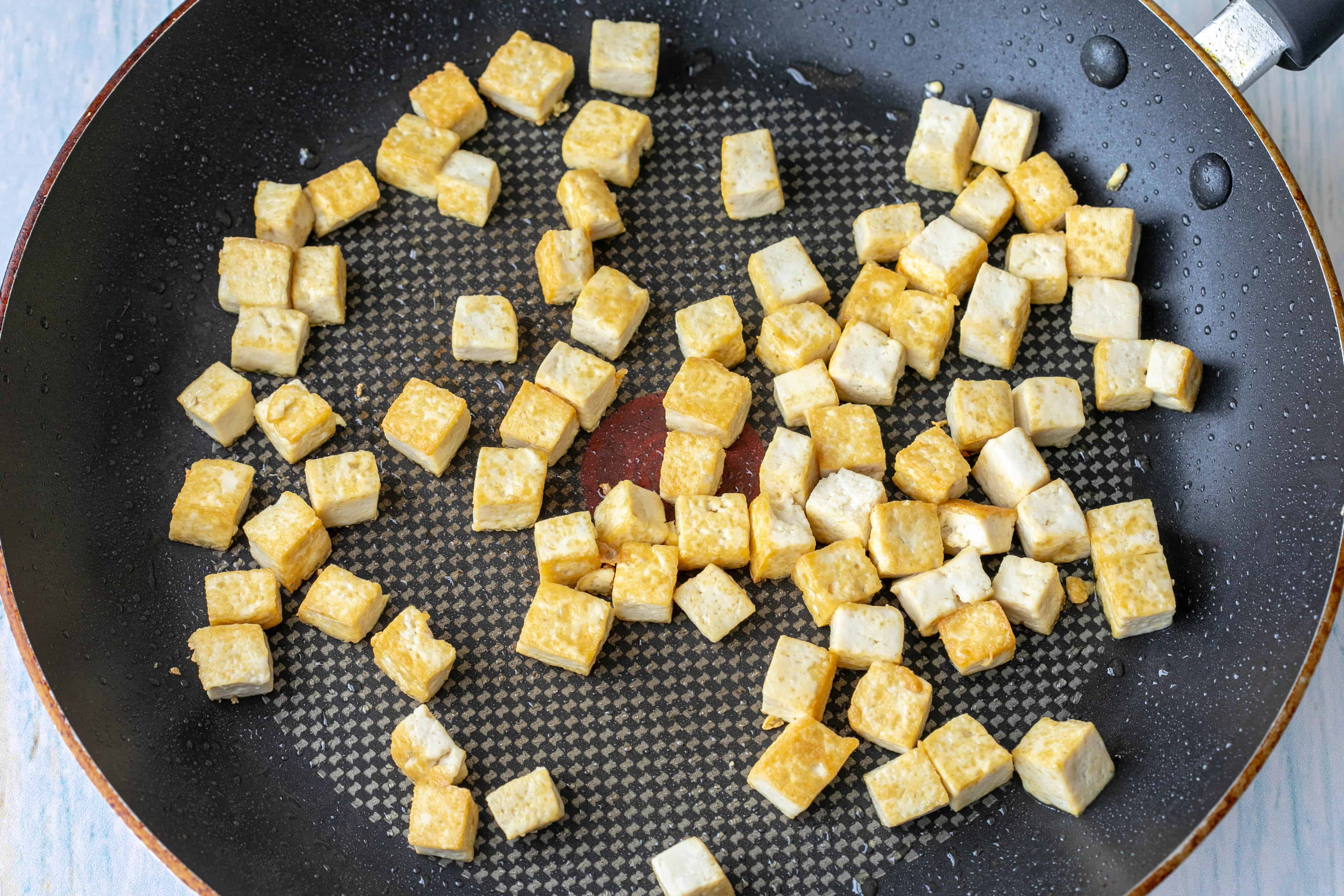 tofu cubes browning in nonstick pan