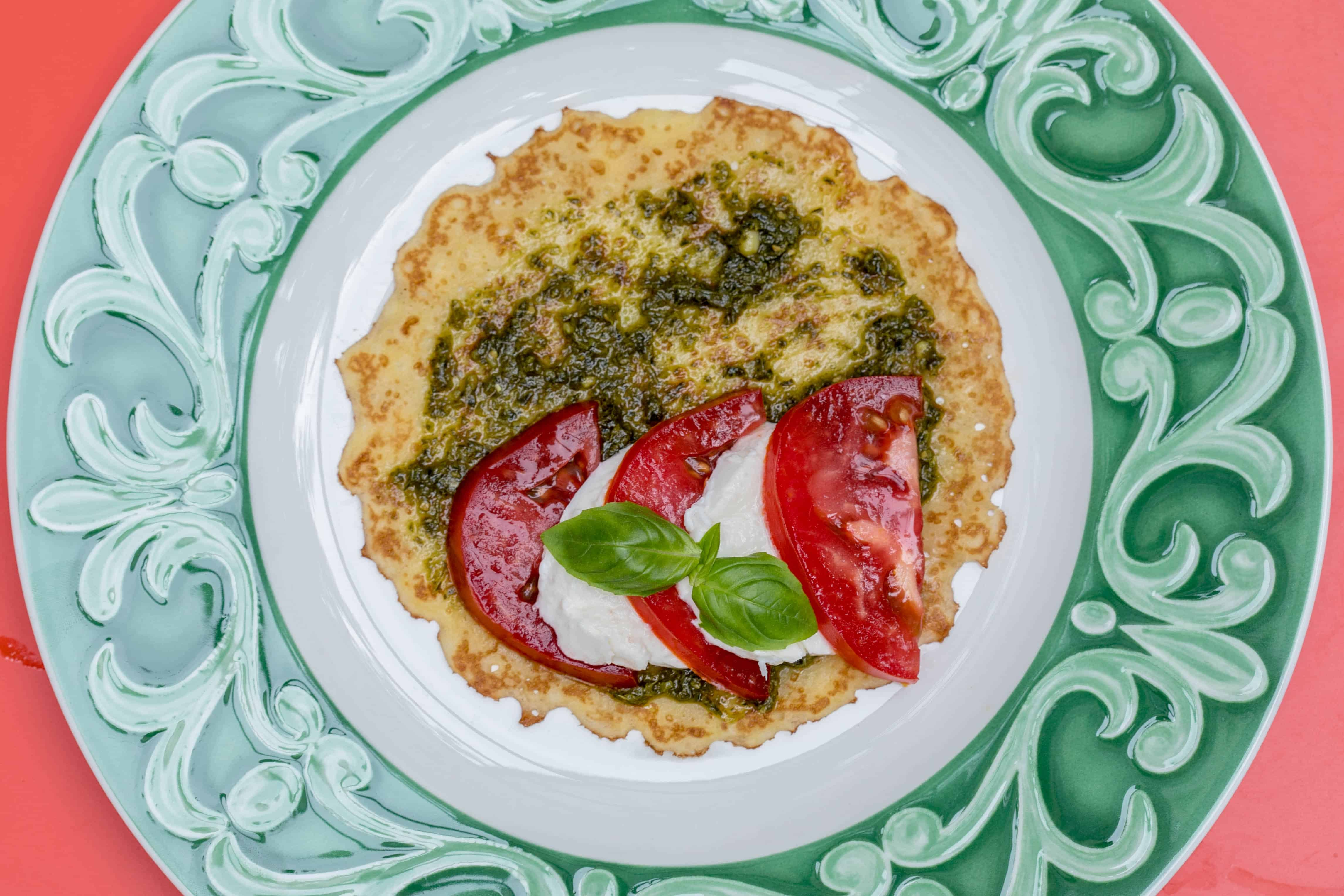 caprese crepe open face on a green and white plate with pesto, tomatoes, mozzarella, and fresh basil