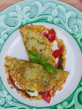 two crepes on a green and white plate filled with tomatoes, mozzarella, and pesto
