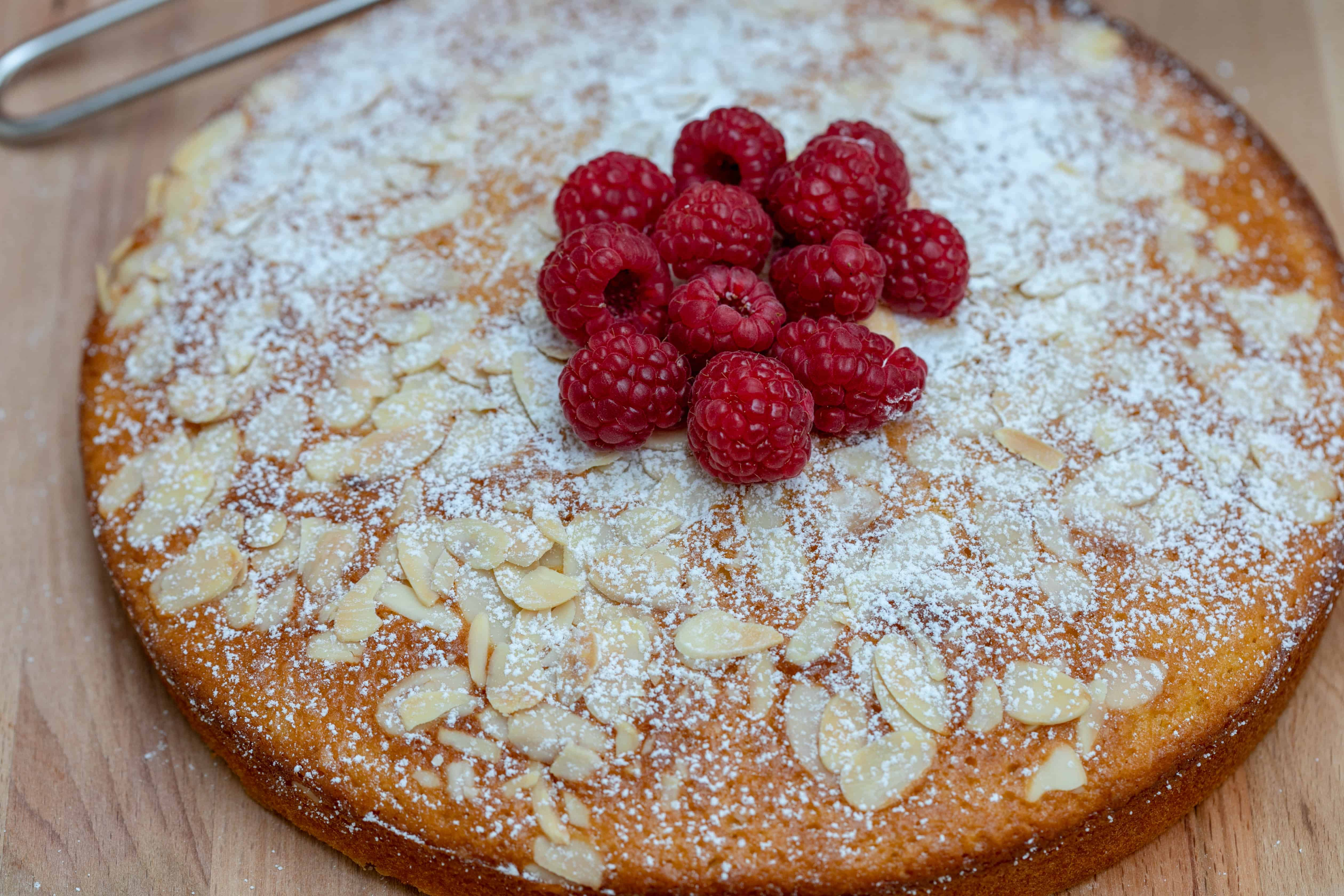French yogurt cake with almonds dusted with powdered sugar and topped with raspberries