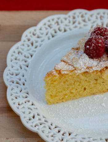 slice of french yogurt cake with almonds topped with powdered sugar and raspberries