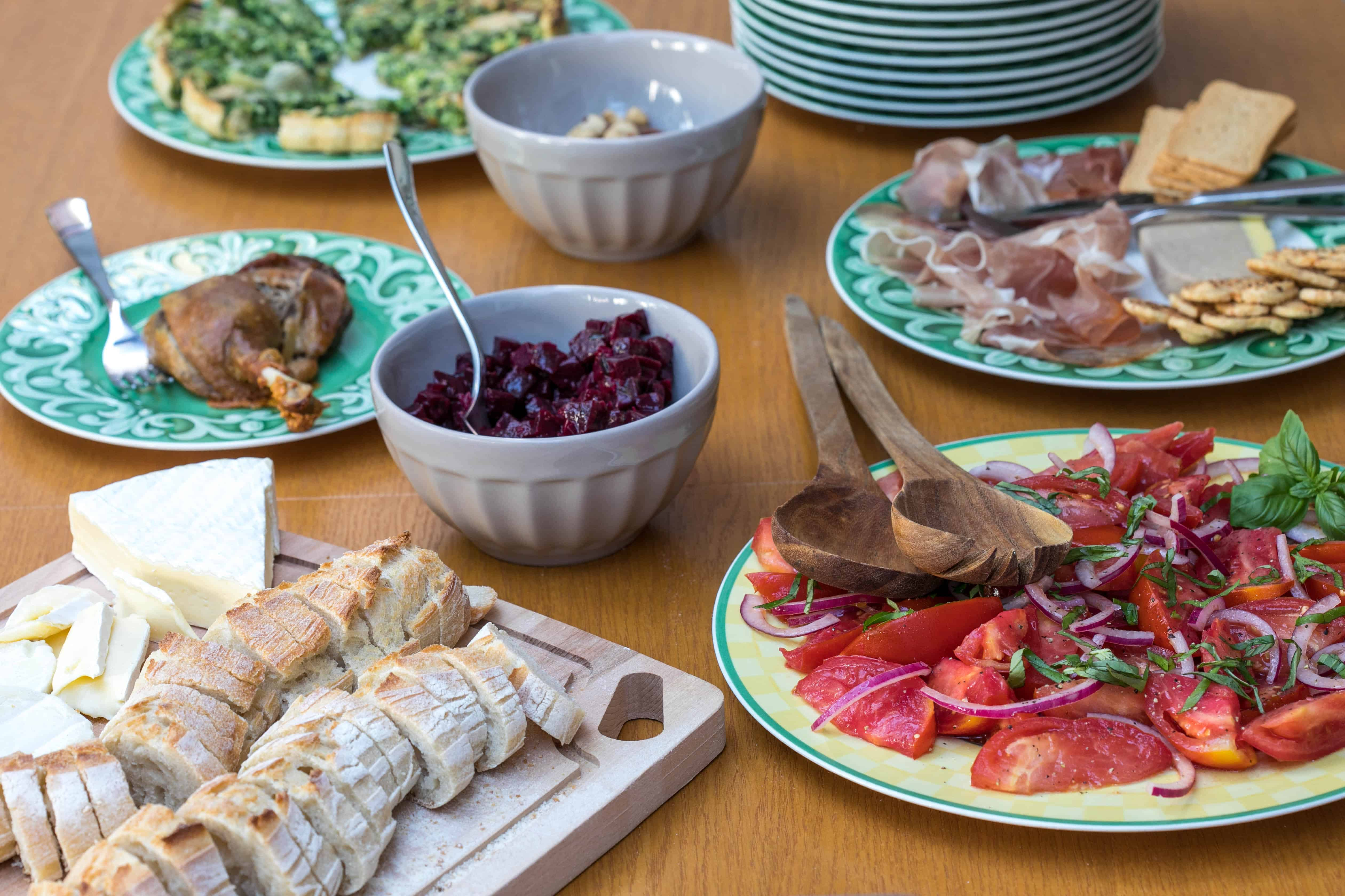 dinner spread with quiche, nuts, duck confit, beets, proscuitto, duck pate, cheese, baguette, and tomato salad