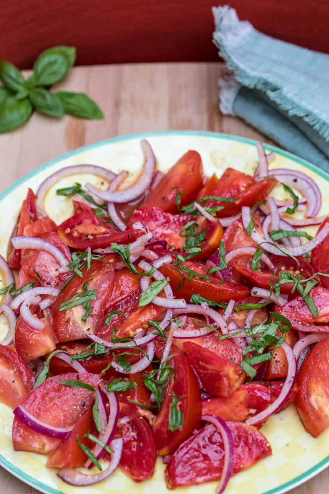 platter of tomato salad with red onions and basil with green napkin
