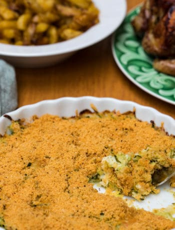 zucchini gratin with green napkin, and roasted potatoes and chicken on plates in background