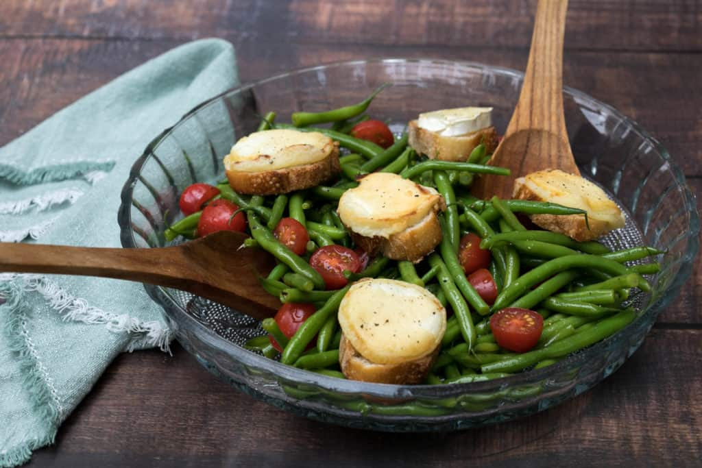 large platter of green bean salad with baked goat cheese