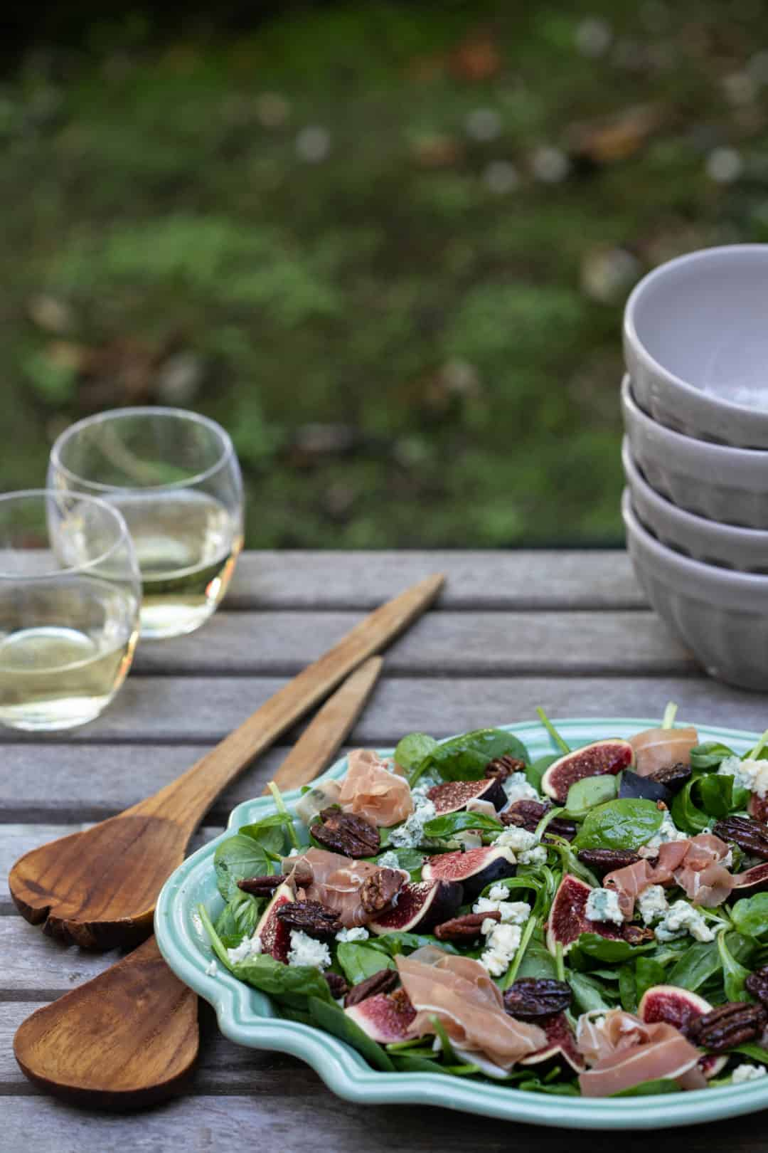 fig salad with blue cheese, pecans, and proscuitto on wooden table outside with glasses of wine, bowls, and serving utensils