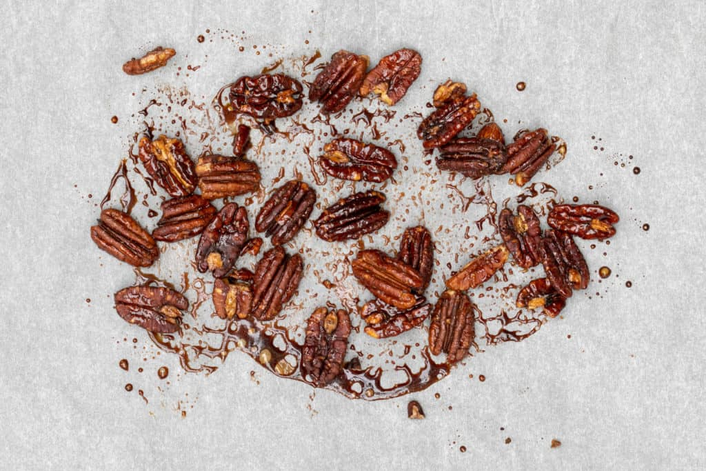 caramelized pecans after baking on parchment paper