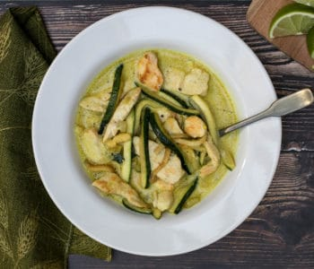 bowl of chicken curry with coconut milk and zucchini with green napkin and lime slices on cutting board