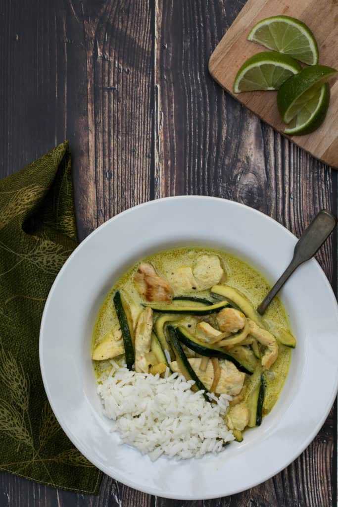 chicken curry with coconut milk and zucchini served with white rice in bowl with napkin and lime slices on the side