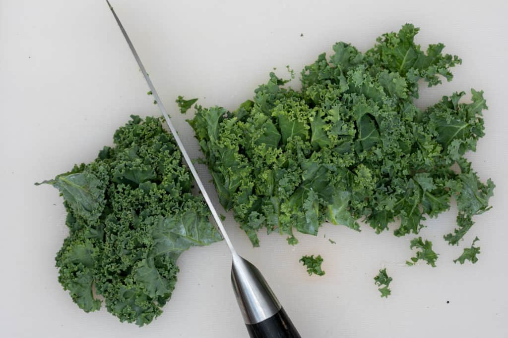 thinly slicing kale with knife