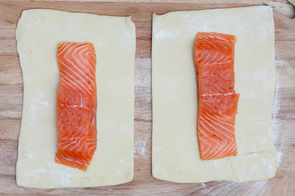 salmon fillets on puff pastry on cutting board