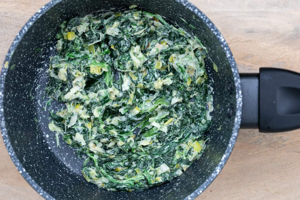 spinach and leeks in cream sauce in small saucepan
