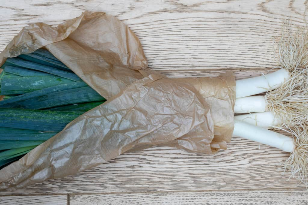 bundle of leeks in brown paper