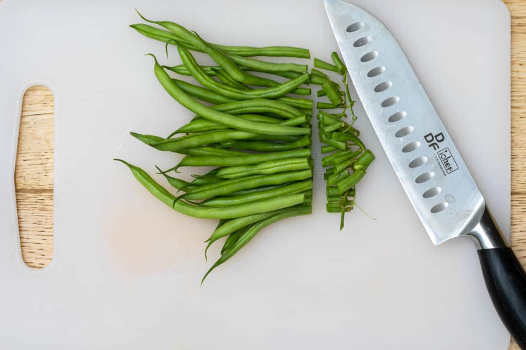 green beans on cutting board with knife (stems cut off)