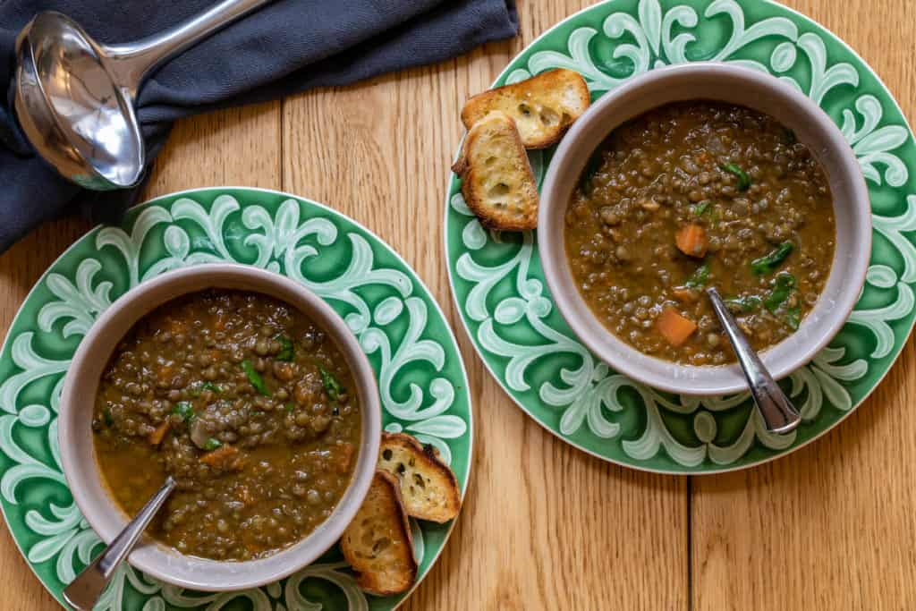 two bowls of french lentil soup with baguette toasts and ladle