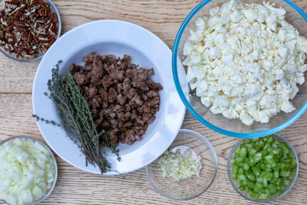 ingredients for cauliflower stuffing: pecans, onions, sausage, thyme, garlic, celery, cauliflower