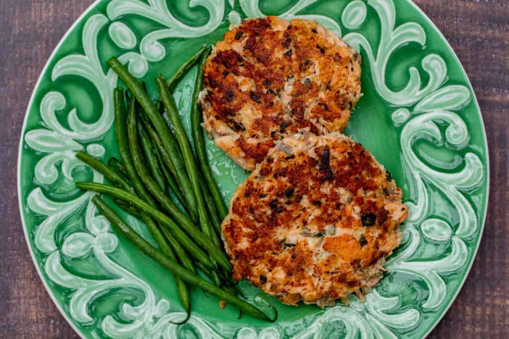 salmon cakes with green beans on green plate