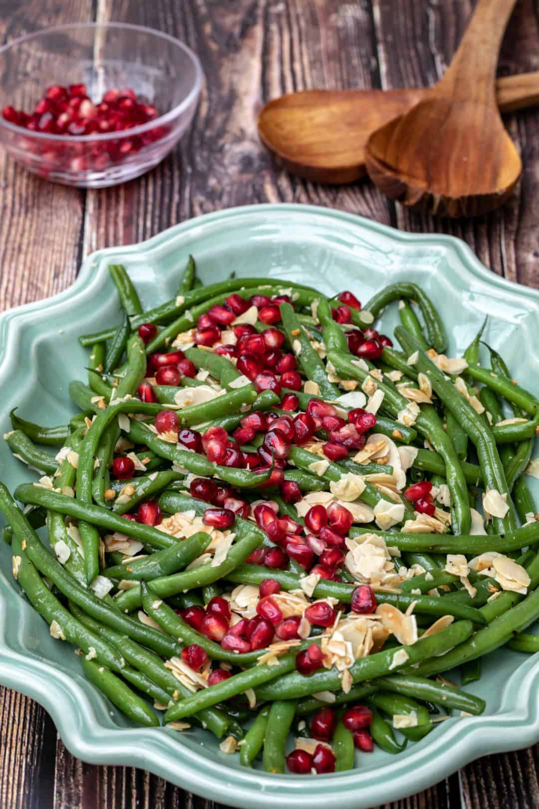 green beans almondine with pomegranate seeds in large platter with seeds and tongs
