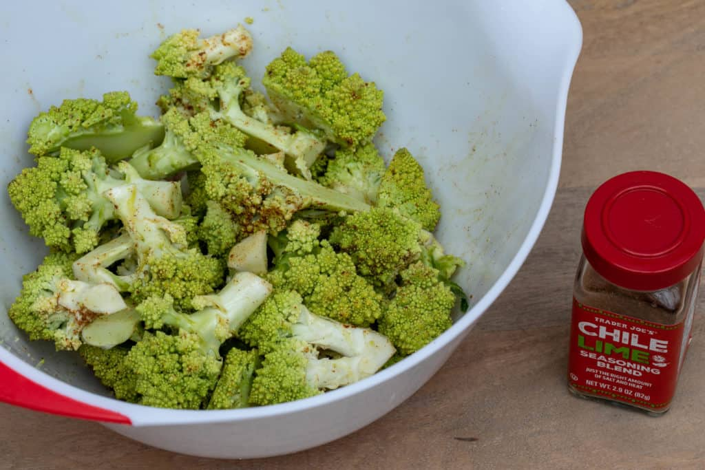 roasted romanesco broccoli in bowl tossed with chile lime seasoning