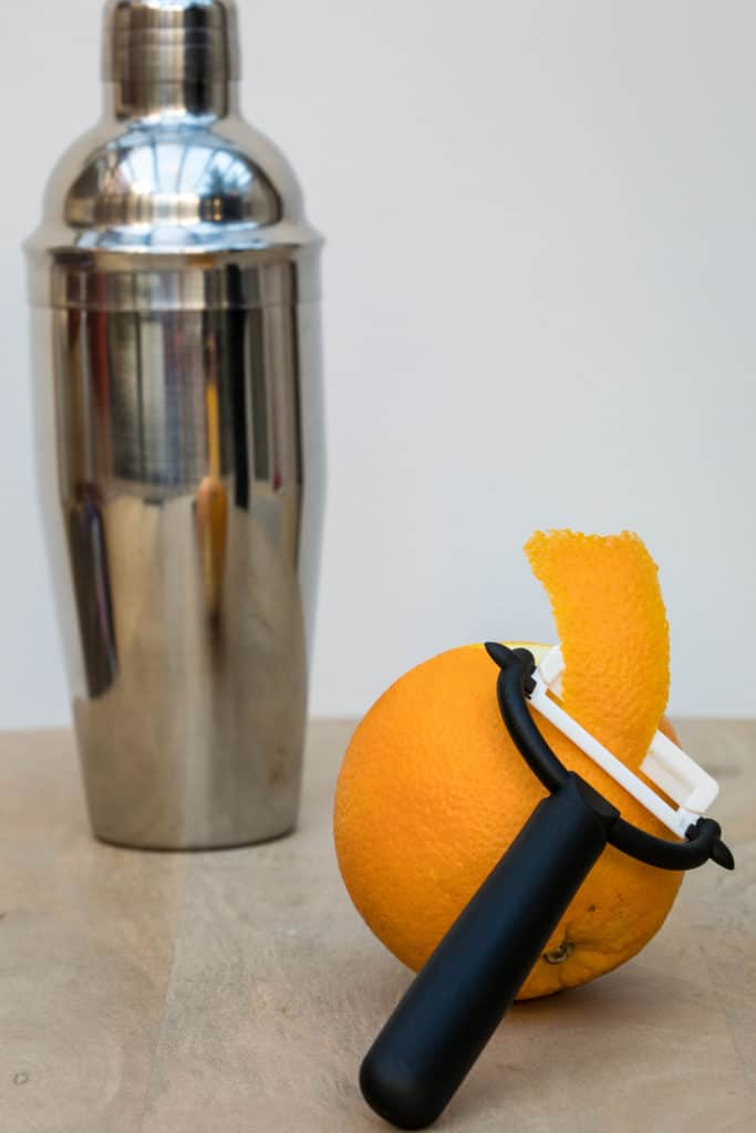 peeling orange twist from an orange with shaker in background