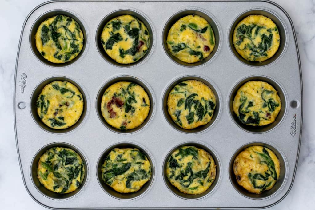 baked spinach bacon egg cups in muffin tin