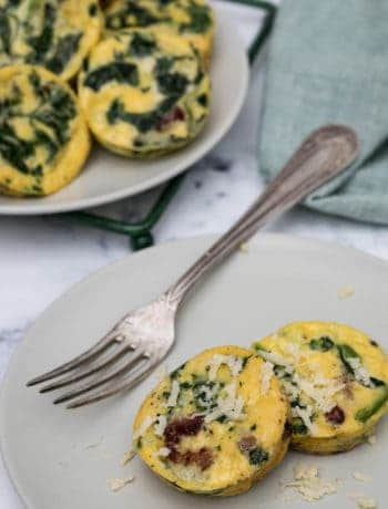 spinach bacon egg cups on plate next to rack of more egg cups