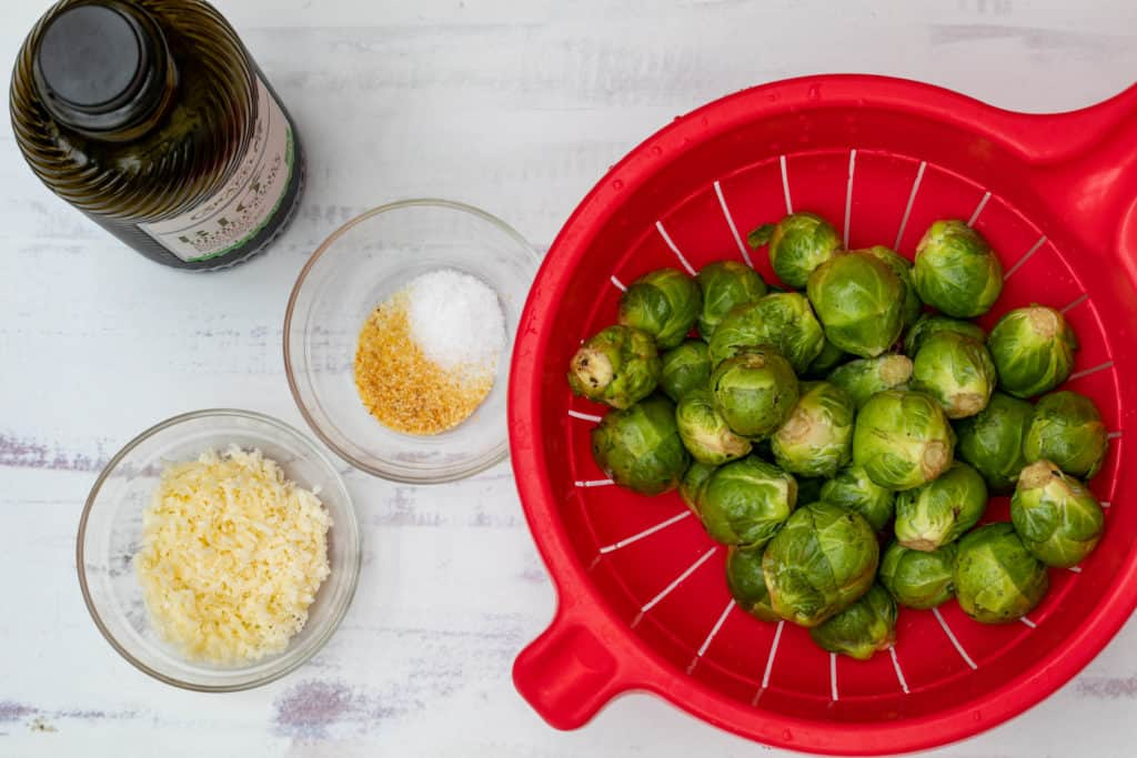 ingredients for smashed brussels sprouts: sprouts, oil, parmesan, garlic powder, and salt