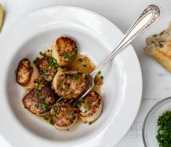 spicy scallop scampi in white bowl with bread, chives, and lemon