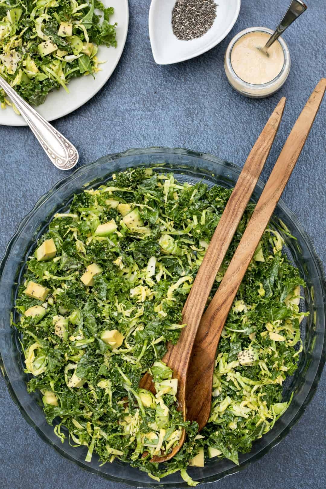 kale and brussels sprouts salad in large bowl with tongs, dressing, and small salad plate
