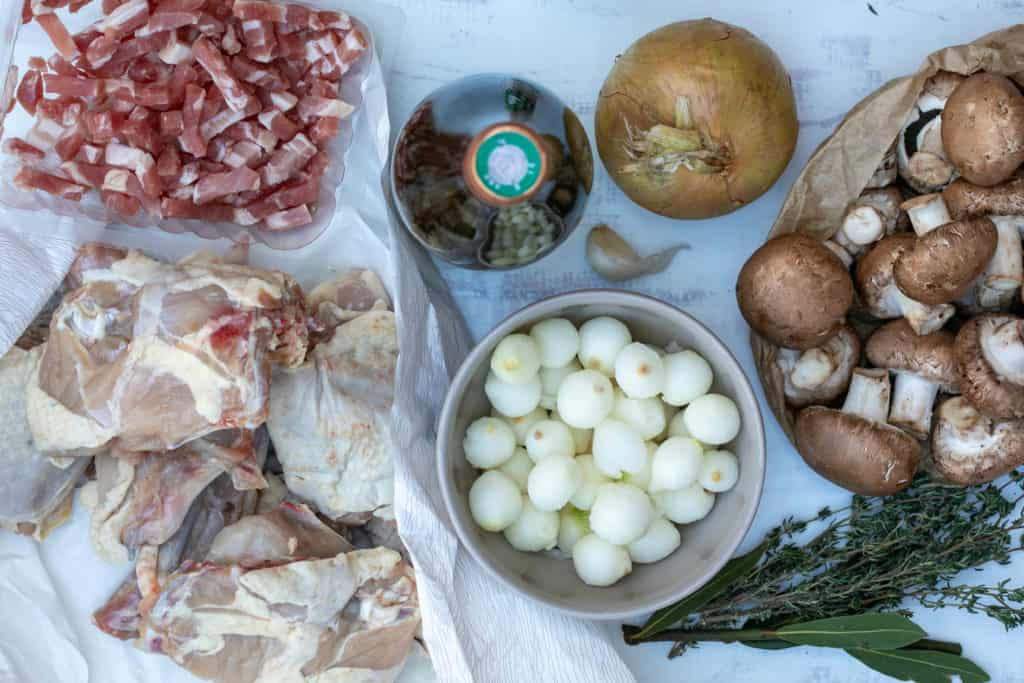 ingredients for coq au vin blanc: chicken, onions, garlic, mushrooms, bacon, white wine, thyme, and bay leaves