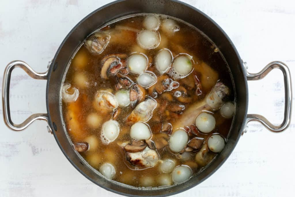 coq au vin blanc ingredients in saucepan, ready to simmer