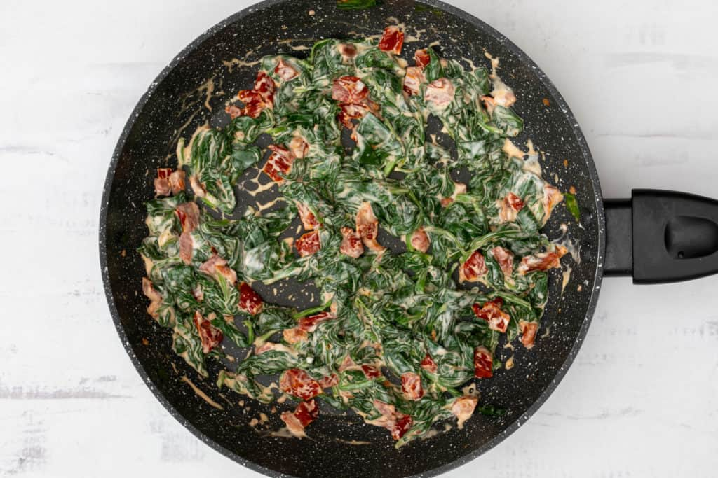 spinach, chopped sun-dried tomatoes, and cream cheese in skillet