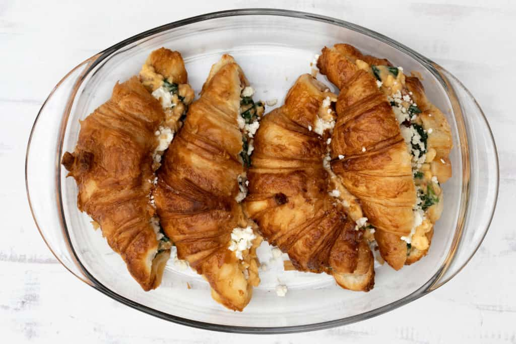 four croissant breakfast sandwiches with spinach and feta in glass baking dish ready for oven