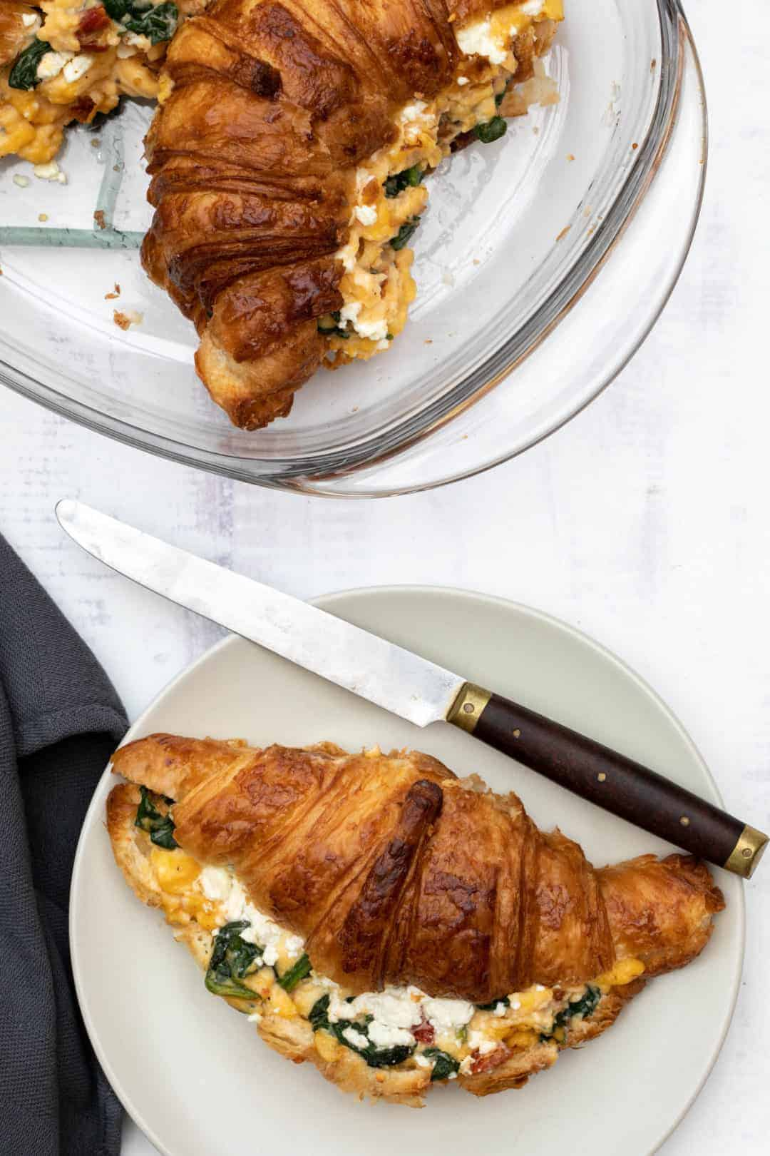 croissant breakfast sandwich on plate with knife and napkin and baking dish