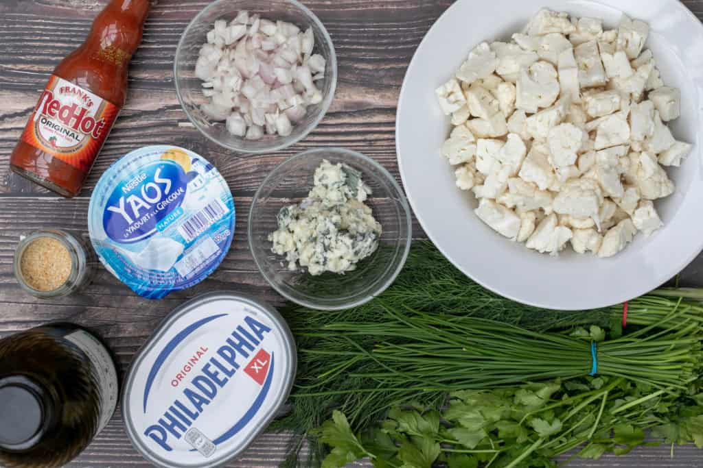 ingredients for buffalo cauliflower dip (cauliflower, herbs, cream cheese, yogurt, blue cheese, shallots, hot sauce)