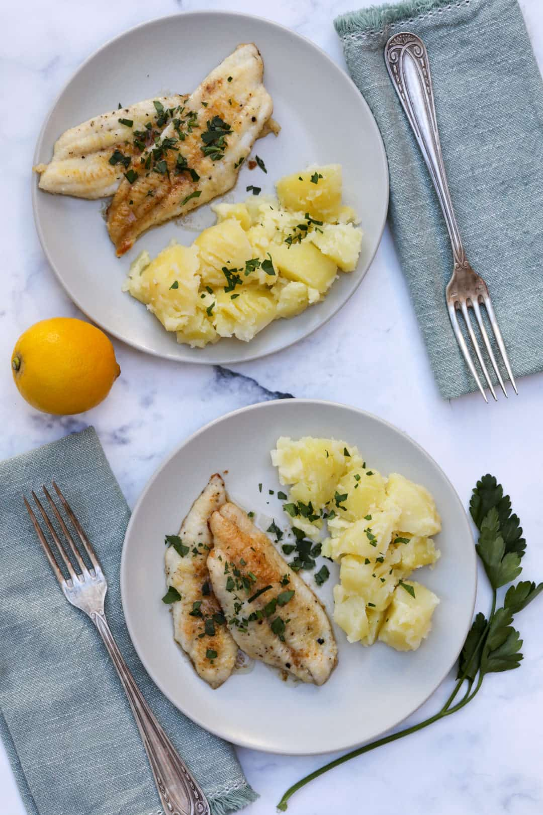Sole meuniere on two plates with forks, napkins, parsley and lemon