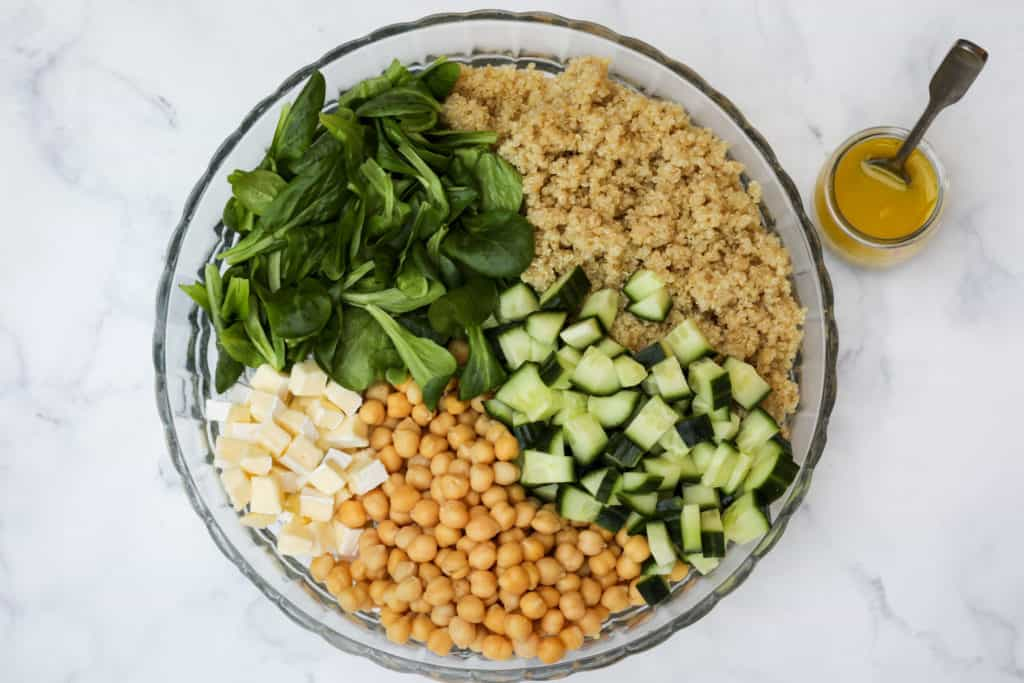 Glass bowl of quinoa chickpea salad with quinoa, cucumber, chickpeas, mache, and brie