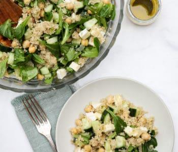 Plate of quinoa chickpea salad next to big bowl of salad and vinaigrette