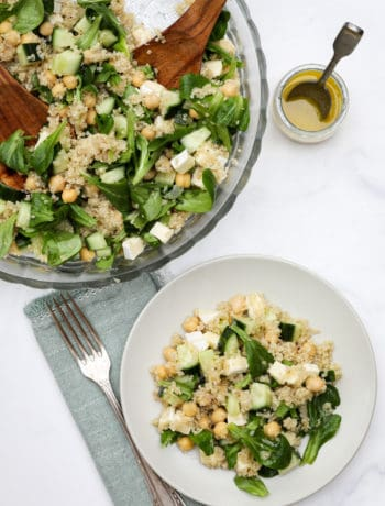 Plate of quinoa chickpea salad next to big bowl of salad and vinaigrette