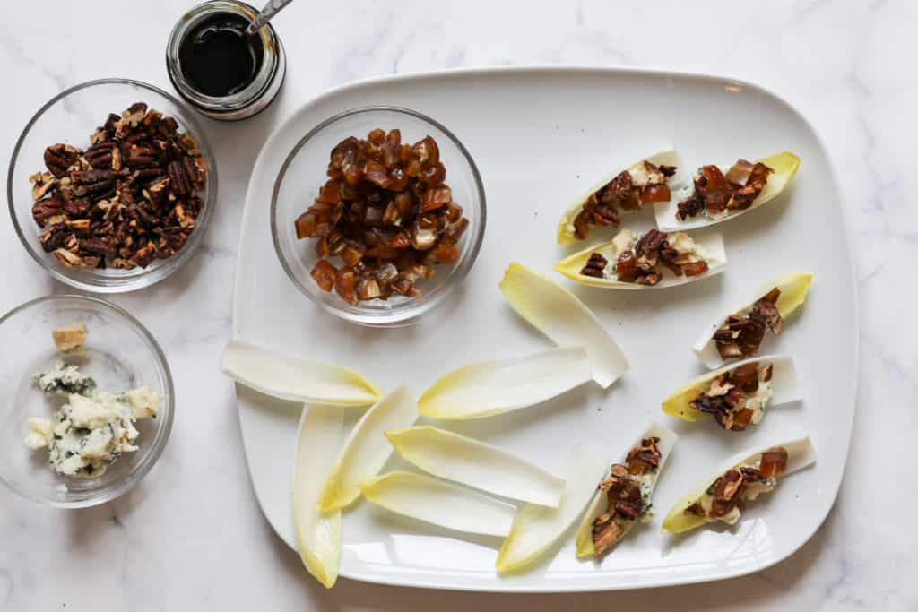 Assembly of blue cheese and pecan endive appetizer on platter