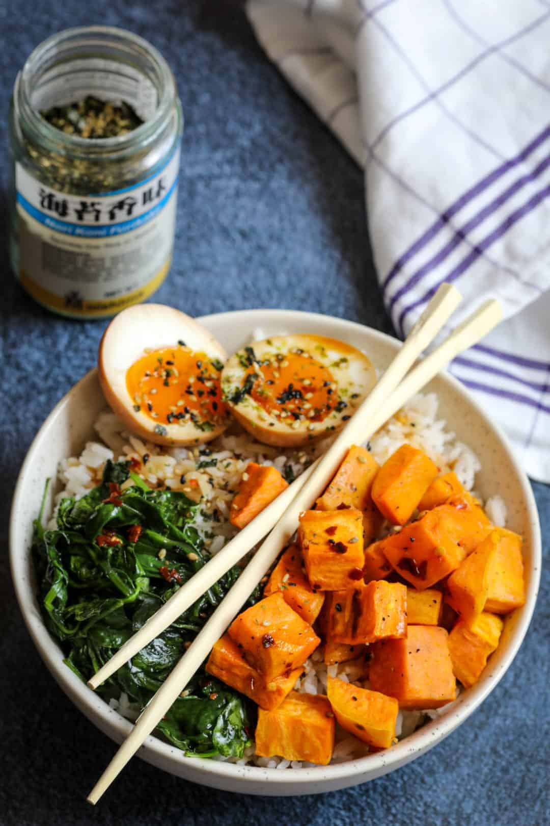 Ramen egg rice bowl in bowl with kitchen towel and furikake