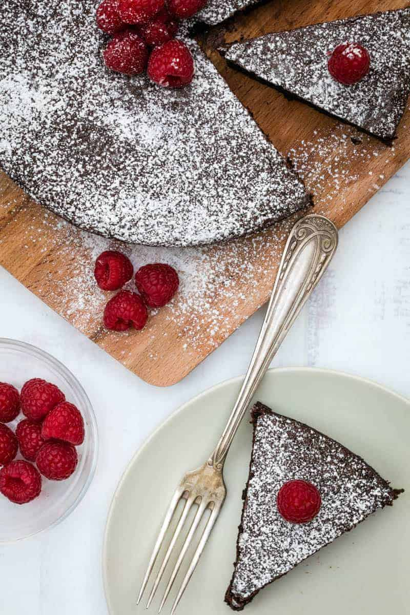 almond flour chocolate cake slice on plate with full cake on cutting board behind, with raspberries