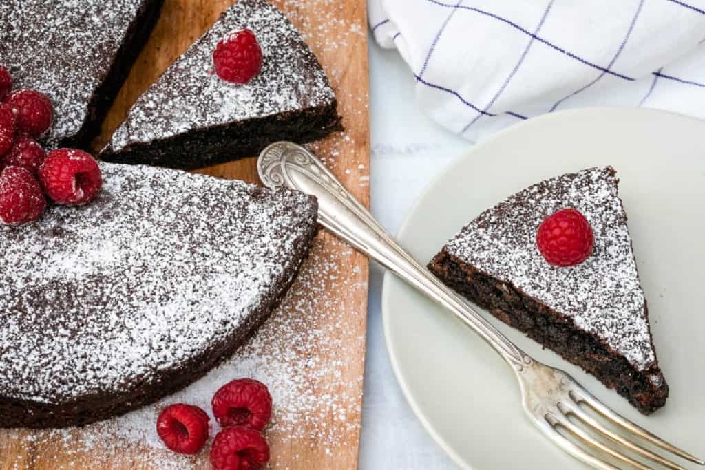 slice of almond flour cake on plate with whole cake on cutting board next to it, with raspberries