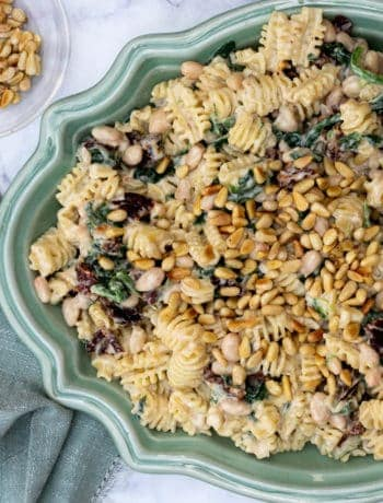 creamy artichoke pasta in serving dish with pine nuts in small bowl and napkin